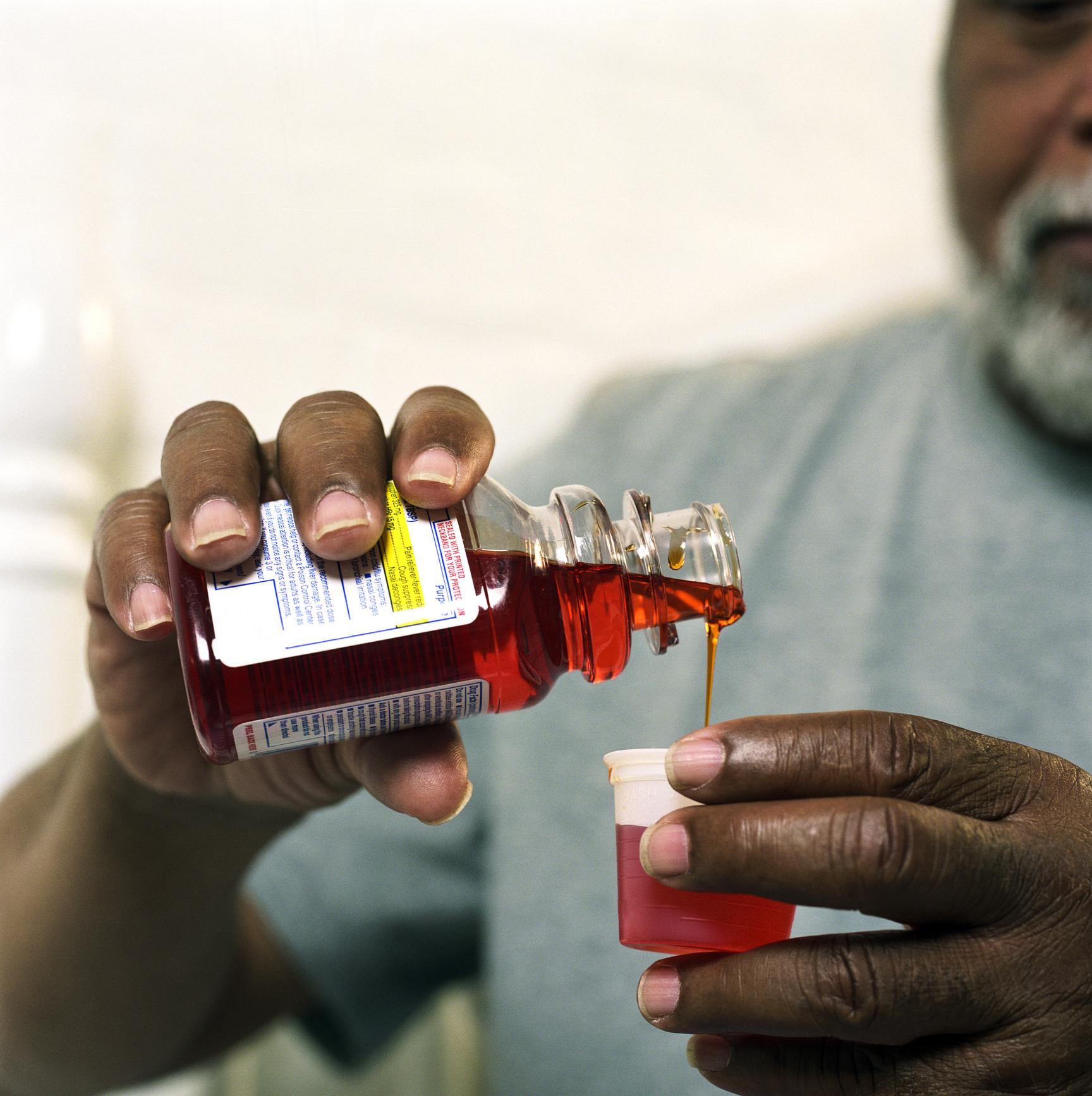 Man pour cold medicine into measuring cup